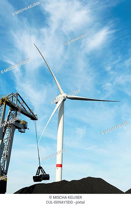 Wind turbine in between piles of coal in harbour, Flushing, Netherlands