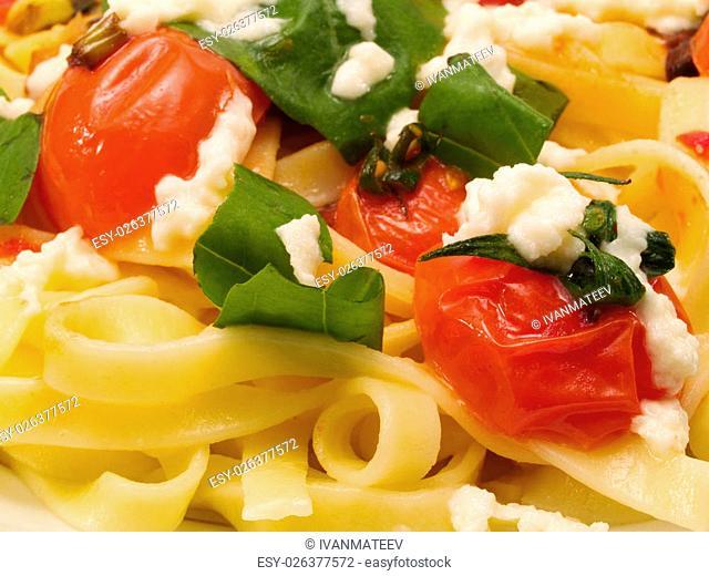 Fettucini prepared with fried cherry tomatoes, basil and mozarella