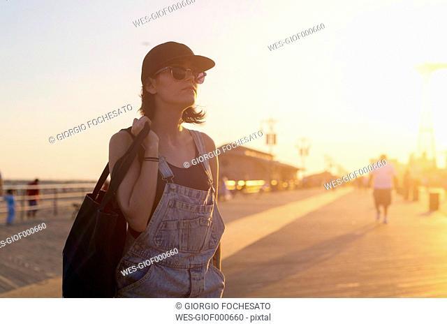 USA, New York, Coney Island, young woman on beach promenade at sunset