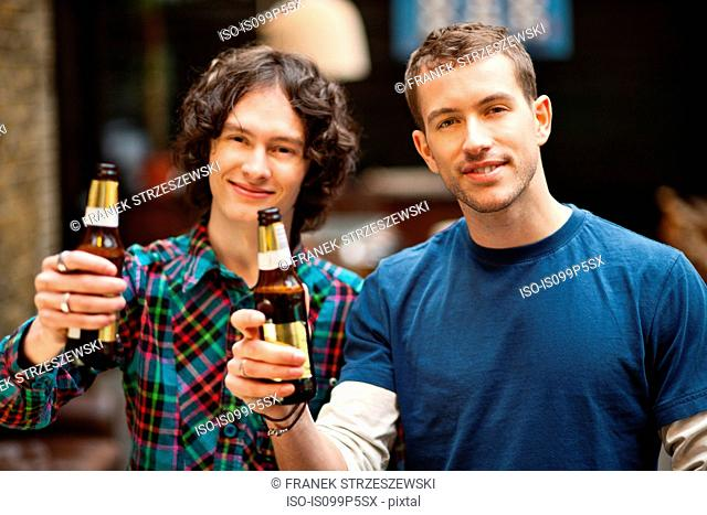 Male friends posing with beer bottles