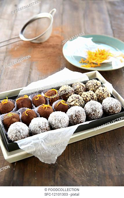 Assorted bliss ball truffles on paper in a chocolate box