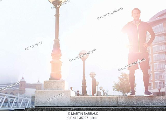 Portrait confident male runner standing at sunny urban lamppost
