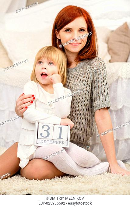 Happy mother and sweet little daughter with date 31 december are sitting on the carpet in the room . Eve of New Year