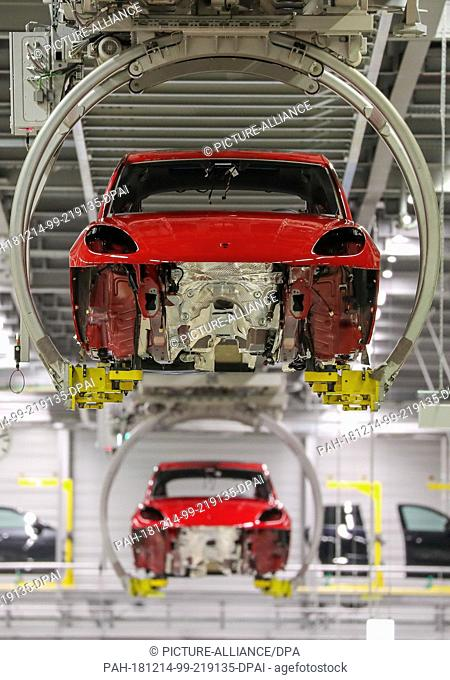 13 December 2018, Saxony, Leipzig: Two unfinished Porsche Macans float through the Porsche plant in Leipzig. The car manufacturer Porsche is preparing for the...