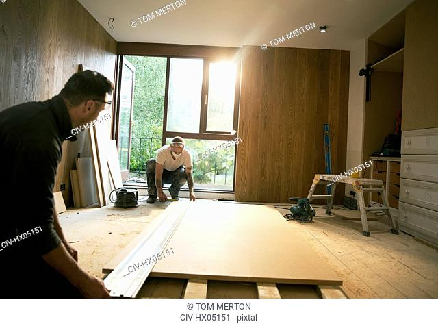 Construction workers measuring wood board in house