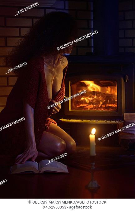 Sensual romantic erotic portrait of a beautiful sexy half naked woman sitting by the fireplace looking at the fire with a book in a cozy warm sweater over her...