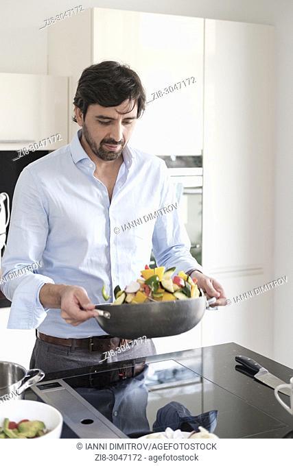 30-35 years old latin man cooking vegetarian food