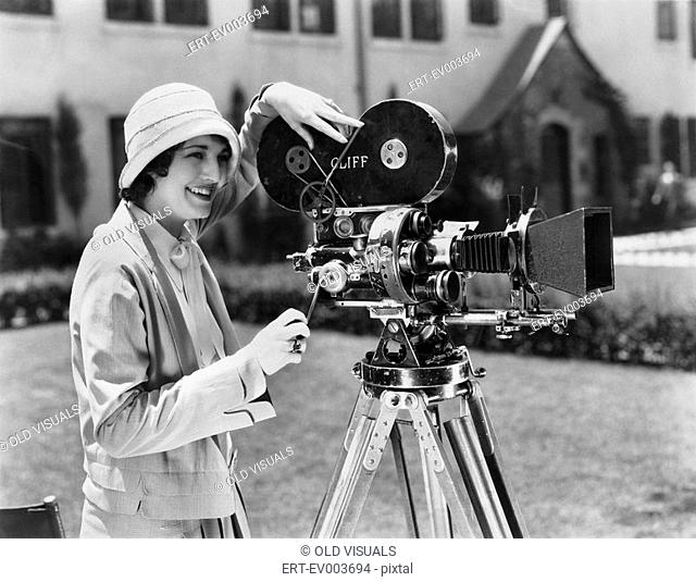 Woman using movie camera outdoors All persons depicted are not longer living and no estate exists Supplier warranties that there will be no model release issues