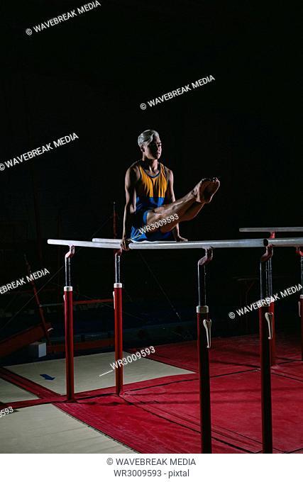 Male gymnast practicing gymnastics on the horizontal bar