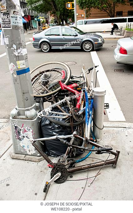 A pile of stripped down bicycles and a garbage bag next to a light pole on a street corner in New York City, USA