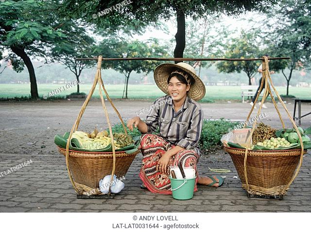 Woman in hat selling fruit. Baskets and carrying pole