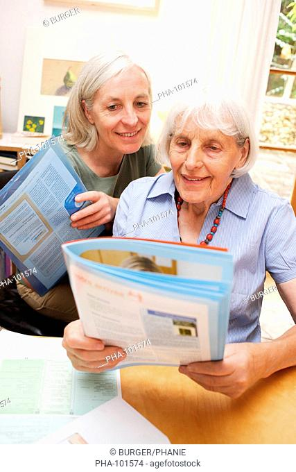 Elderly woman reading a brochure on service or facility dedicated to elderly person nursing home, hospital, insurance, banking, etc