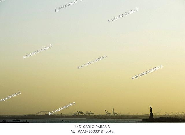 United States, New York City, New York Harbor at sunrise, Statue of Liberty visible in distance