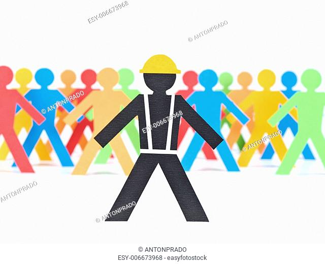 A paper construction worker stands out from the multicolored crowd. Selective focus. White background
