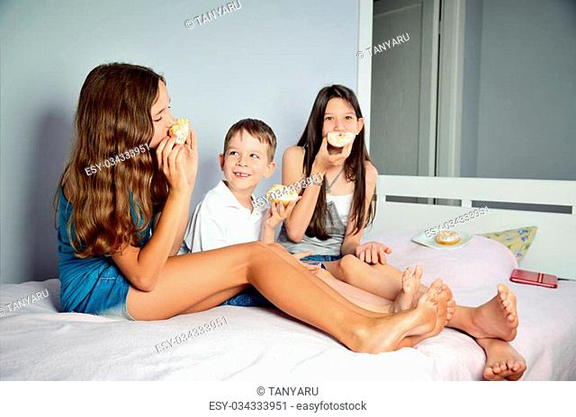 funny kids are sitting in bed and eating donuts. horizontal