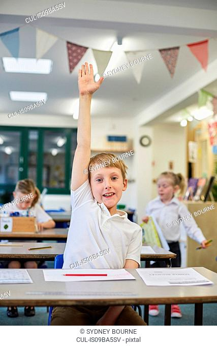 Schoolboy with hand up in classroom at primary school