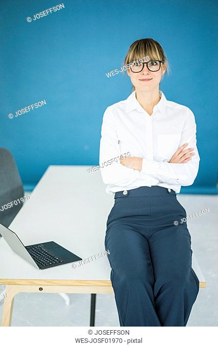 Portrait of smiling businesswoman with laptop in office