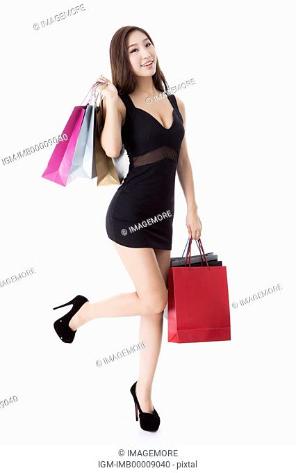 Young woman standing with one leg and holding shopping bags