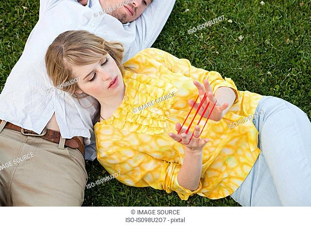 Young couple outdoors, woman playing with string