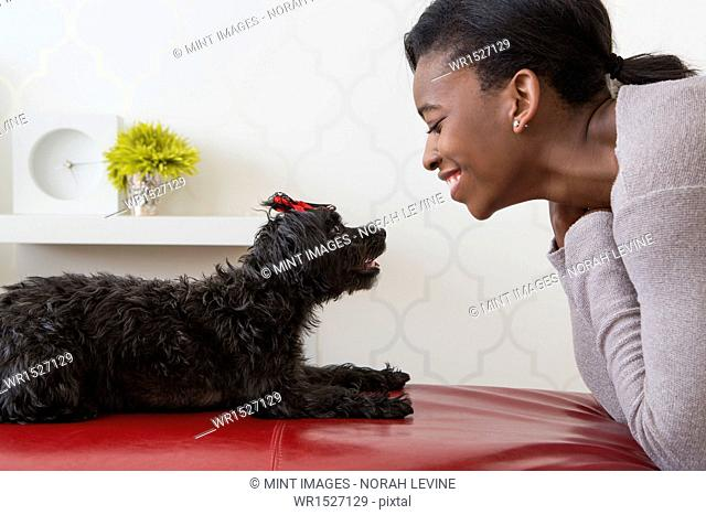 A young girl playing with her small black pet dog