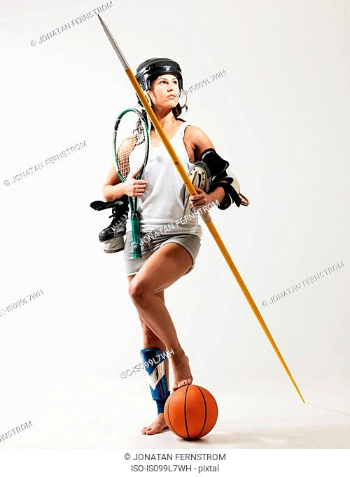 Young woman holding sports equipment against white background
