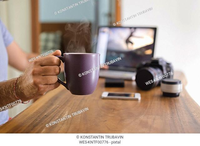 Photographer holding coffee cup at desk at home