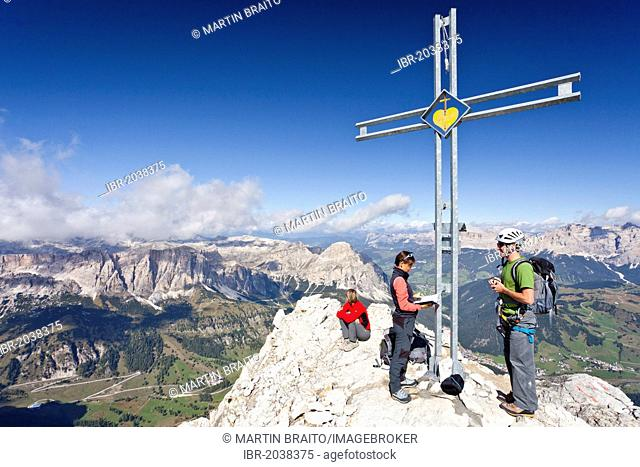 Mountain climbers at the summit cross of Boeseekofel Mountain, looking towards the Fanes Group and the Heiligkreuzkofel Group, Dolomites, Trentino, Italy
