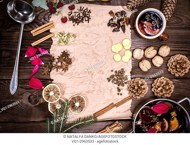 paper bundle of brown paper and ingredients for making mulled wine on a brown wooden background, empty space in the middle