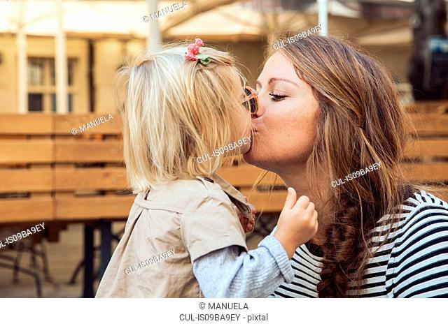Mother kissing toddler daughter on park bench