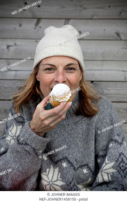 Portrait of woman wearing warm clothing eating cake