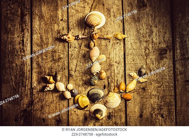 Rustic decorative seaside art on a maritime anchor made with various sized ocean shells on wooden planks background. Nautical beach house details
