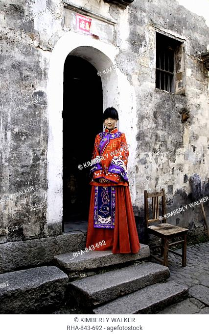 Young bride in red traditional Chinese bridal dress outside her ancient home, Hongcun village, Anhui province, China, Asia