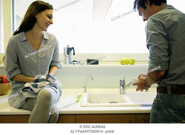 Couple washing dishes together