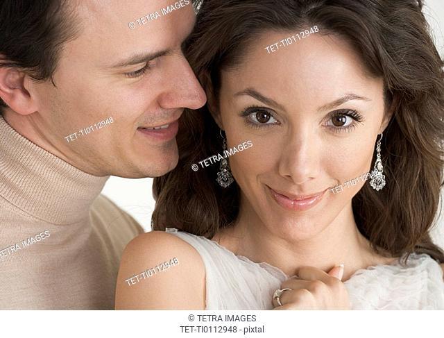 Man whispering in woman's ear