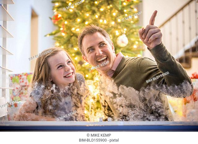 Caucasian father and daughter peering out frosty window at Christmas