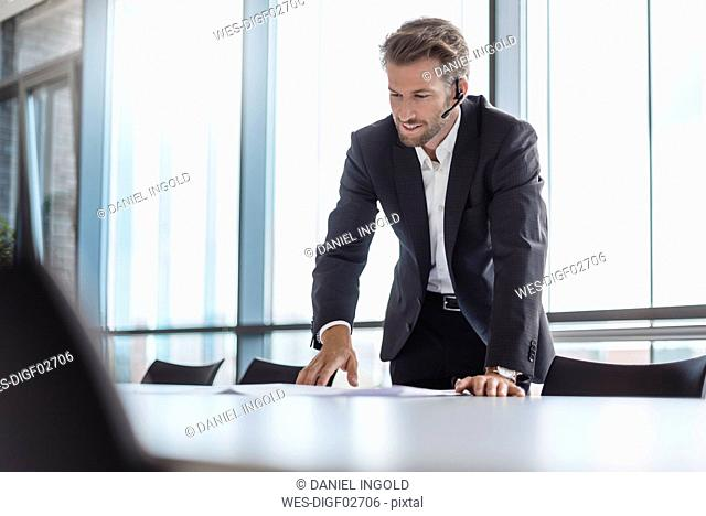 Businessman with bluetooth headset standing in conference room explaning
