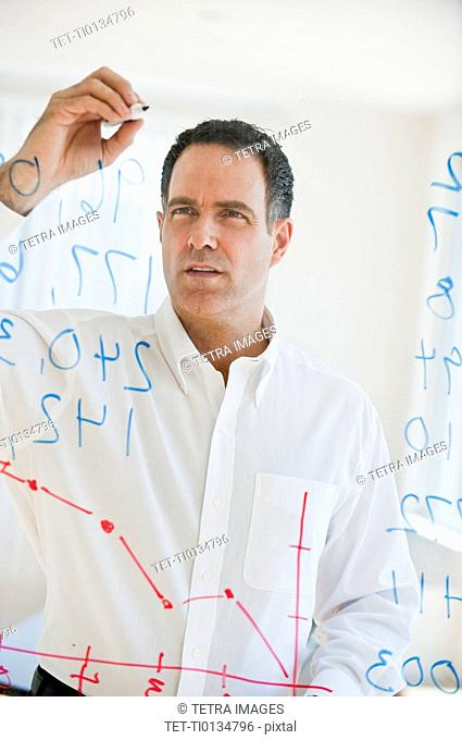 Mature businessman writing numbers on transparent glass wall