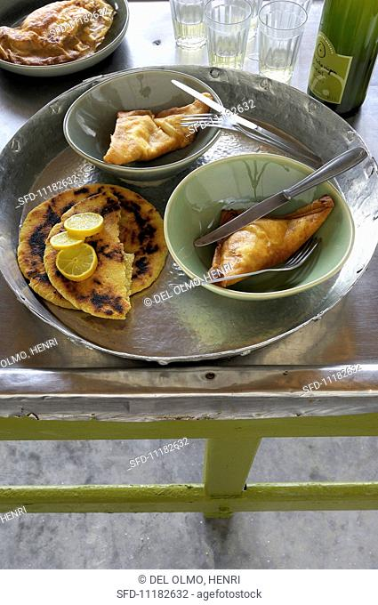 Brik pastry parcels filled with ricotta and tomatoes, with flatbread (Tunisia)