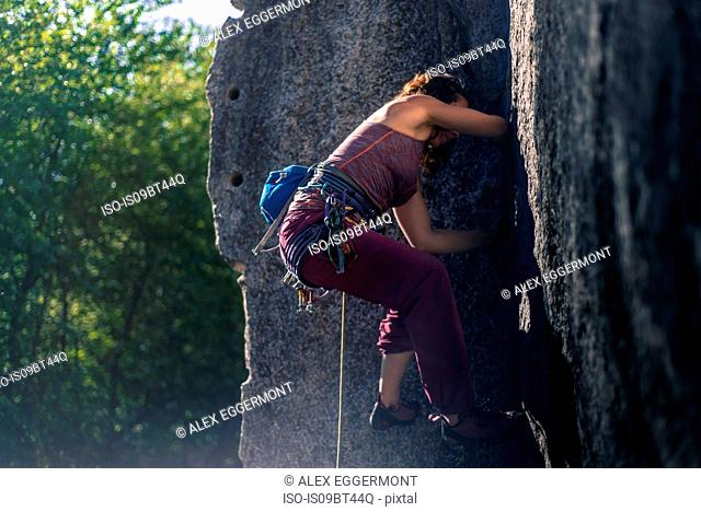 Young female rock climber climbing rock face, full length, side view, Smoke Bluffs, Squamish, British Columbia, Canada