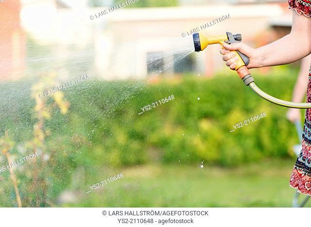 Lifestyle summer scene. Woman watering garden plants with sprinkler