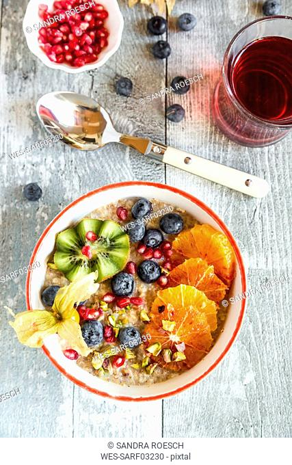 Superfood breakfast with porridge, amaranth, various fruits and pistachios