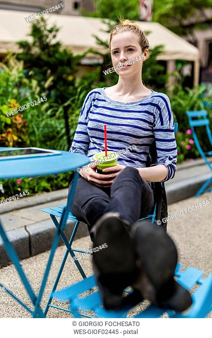 Young woman having a break drinking a smoothie outdoors