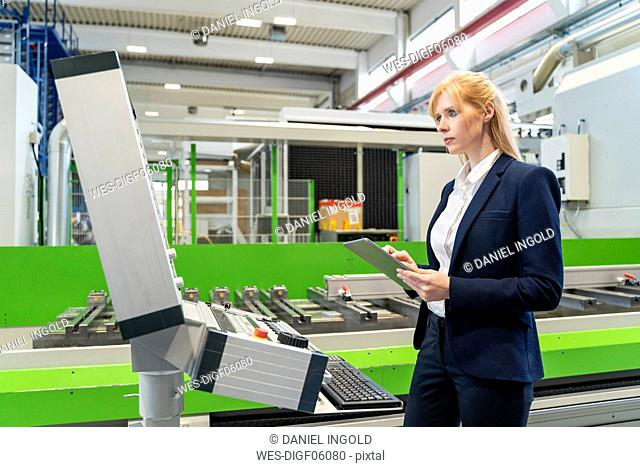 Businesswoman using tablet at machine in factory