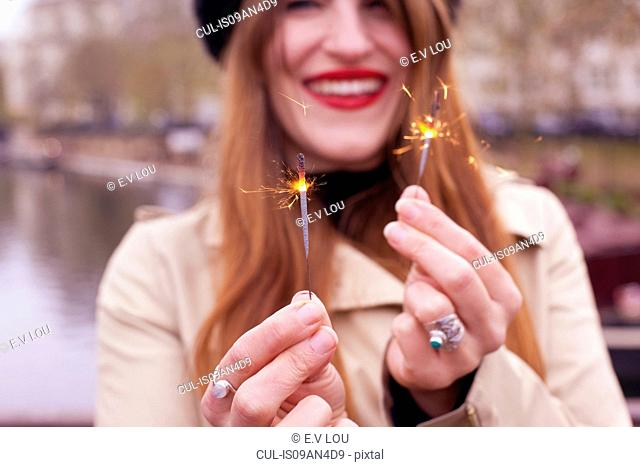 Portrait of woman holding mini sparklers