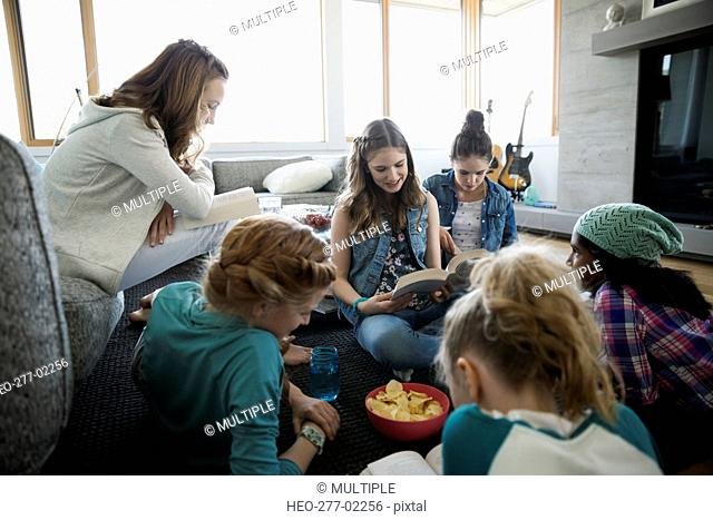 Girls reading books in living room