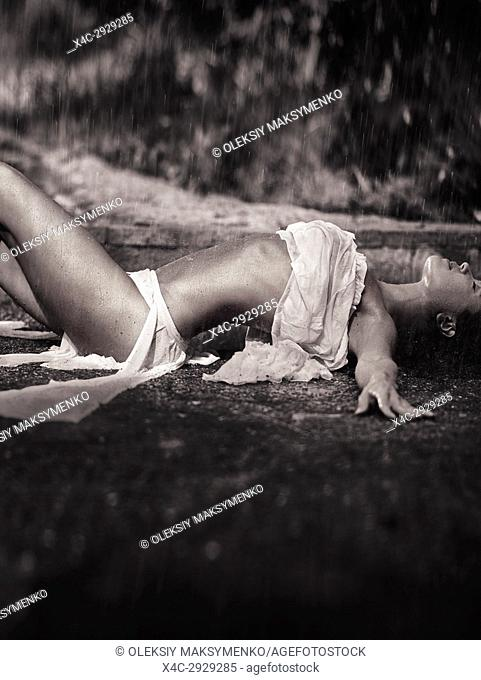 Beautiful barely clothed sexy young woman in beach wear lying wet on the ground under pouring summer rain