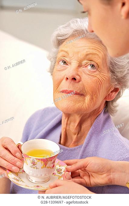 senior woman in a mauve cardigan, and young help giving her a cup of tea at home