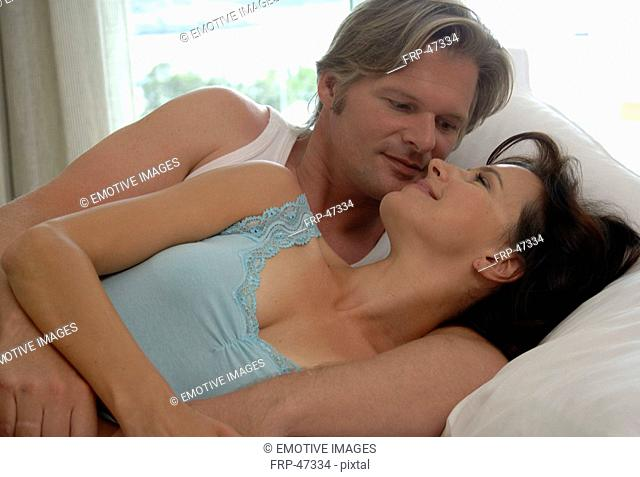 Couple lies in bed