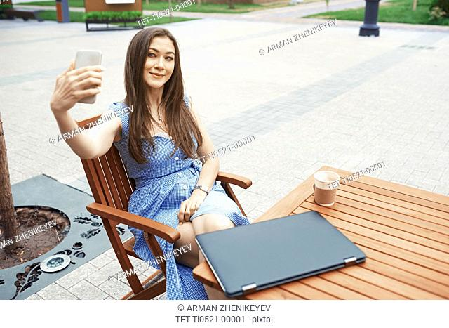 Woman taking selfie at outdoor cafe table