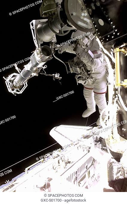 Astronaut Jeffrey N. Williams, mission specialist, works to attach the newly delivered main boom of the Russian crane Strela to its operator post which had been...